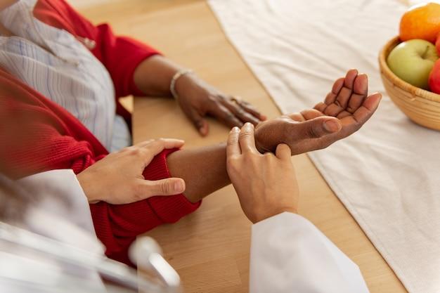 Comprobando el pulso. enfermera vistiendo chaqueta blanca comprobando el pulso para mujer vistiendo cardigan rojo