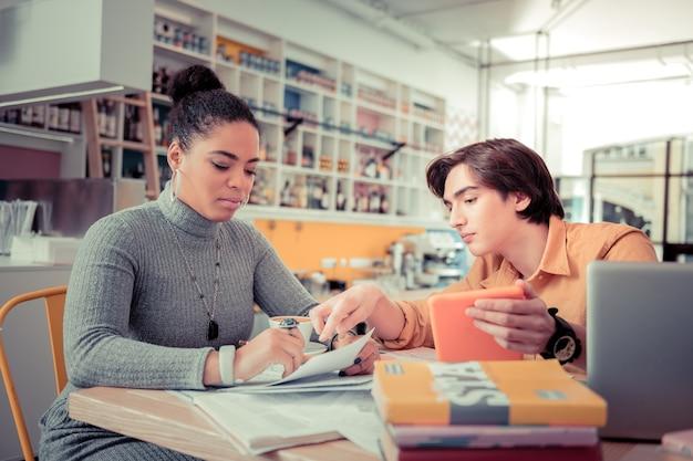 Comprobando respuestas en línea. estudiantes que verifican las respuestas de sus exámenes en línea juntos usando una tableta