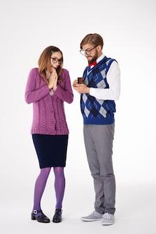 Compromiso de pareja joven geek de aspecto divertido aislado