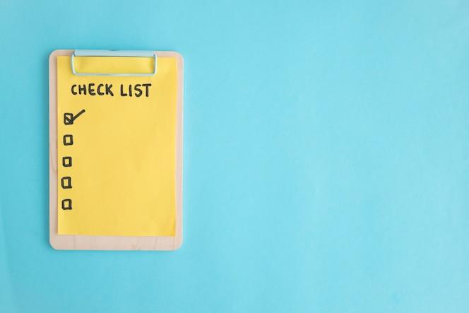 Compruebe el papel de la lista en el sujetapapeles de madera sobre el fondo azul