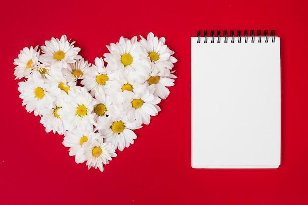 Compuesto en forma de corazón con flores y bloc de notas.
