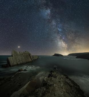 Compuesto de paisaje nocturno en la playa de la costa norte de españa.