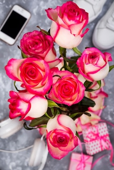 Compuesto por las rosas y el teléfono móvil en la parte posterior de un fondo borroso