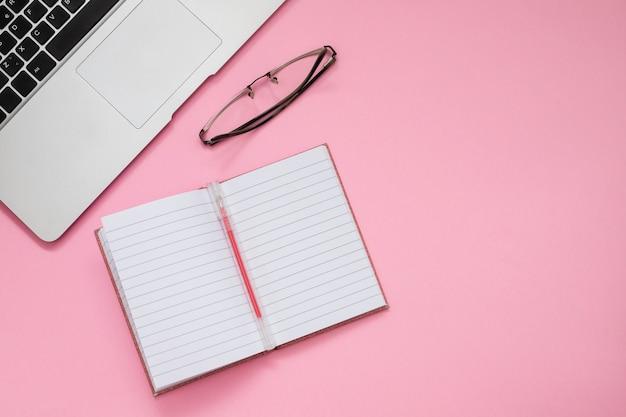 Computadora y billetera sobre fondo rosa