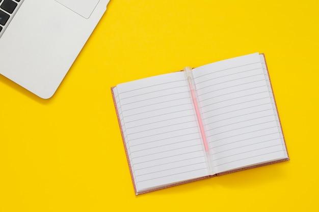 Computadora y bolsillo sobre fondo amarillo