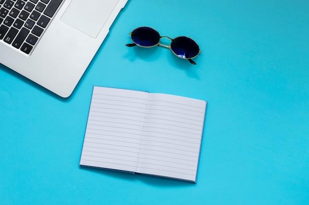 Computadora y bolsillo sobre fondo azul.