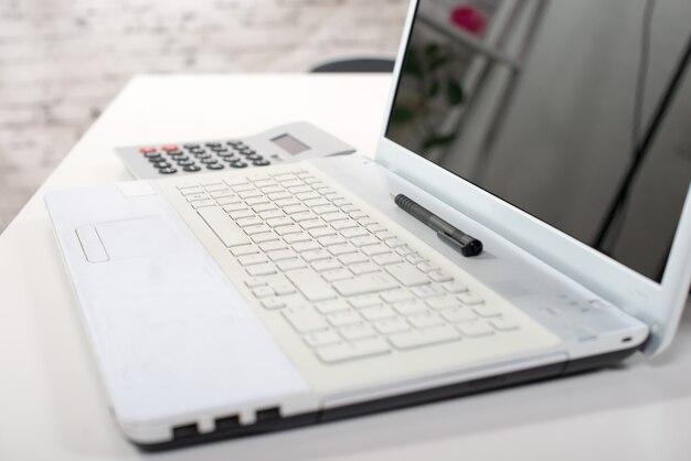 Una computadora, una calculadora y un bolígrafo sobre un escritorio