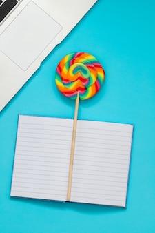 Computadora, dulces brillantes y bolsillo sobre fondo azul.
