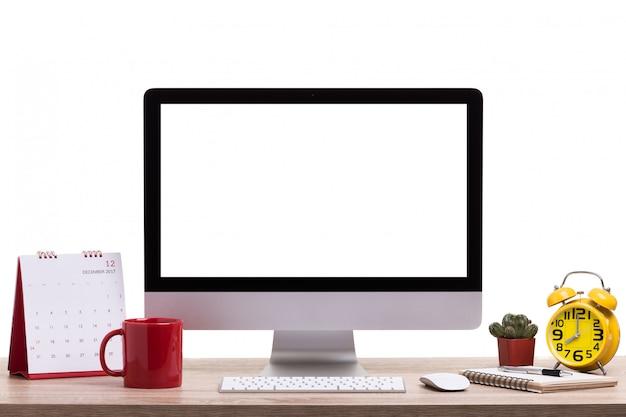 Computadora de escritorio moderna, taza de café, reloj despertador, cuaderno y calendario en mesa de madera. pantalla en blanco para montaje de visualización de gráficos