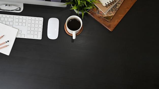Computadora de escritorio de oficina y suministros de oficina con café en mesa negro.
