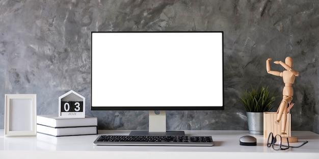 Computadora de escritorio con pantalla en blanco en una habitación de oficina mínima con decoraciones y espacio de copia