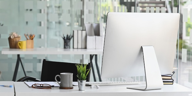 Computadora del espacio de trabajo colocando un escritorio de trabajo blanco rodeado de una taza de café, una planta en maceta, un documento, una pila de libros, un teclado inalámbrico y un mouse sobre la oficina moderna