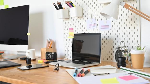 Computadora de espacio de trabajo con mesa de diseño gráfico en estudio real.