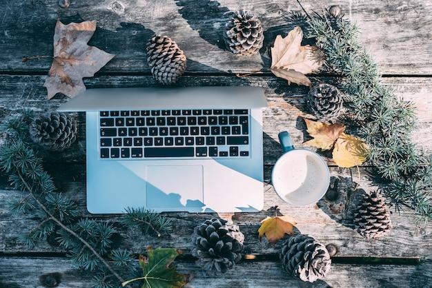 Computadora en una mesa de madera con café y pinos al aire libre