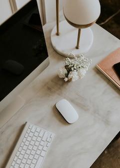 Computadora en una mesa de mármol junto a una lámpara