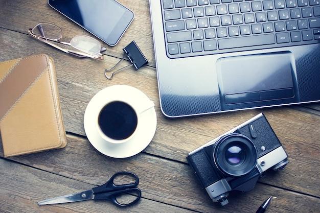 Computadora de mesa de trabajo, cámara, teléfono, café, cuaderno, gafas, tijeras en una mesa de madera
