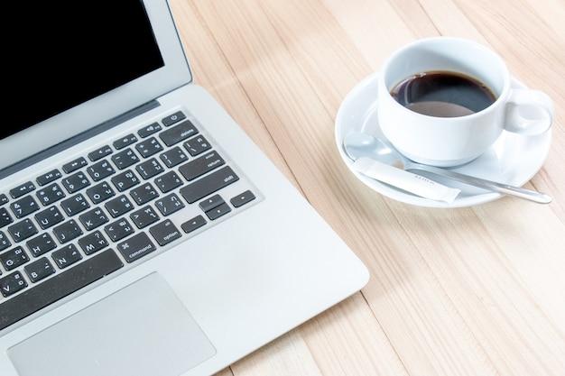 Computadora nootbook, laptop puesta cerca de taza de café puesta en mesa de madera