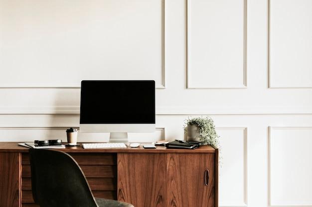 Computadora por un planificador diario sobre una mesa de madera