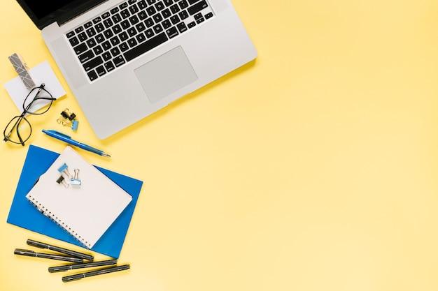 Una computadora portátil abierta con papelería de oficina sobre fondo amarillo