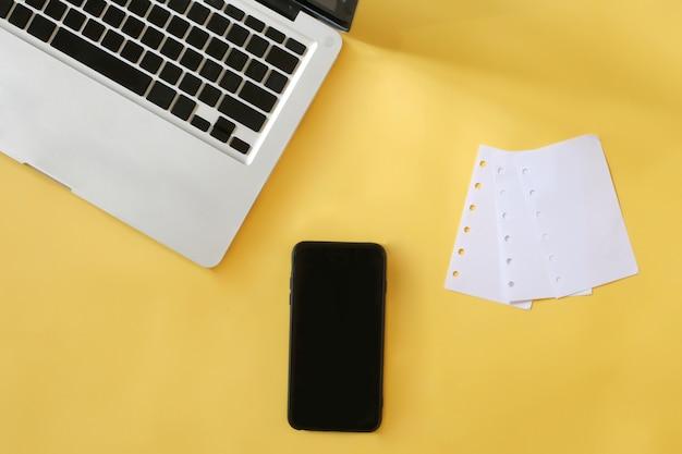 Computadora portátil amarilla de la maqueta del fondo del negocio con la nota y smartphone