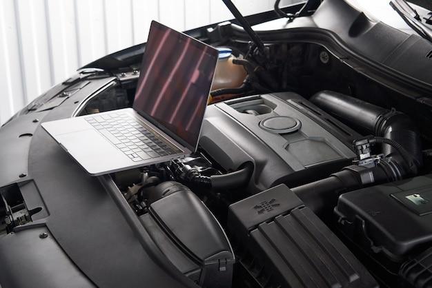 Computadora portátil en un automóvil en taller de reparación de automóviles, concepto mecánico reparador de automóviles