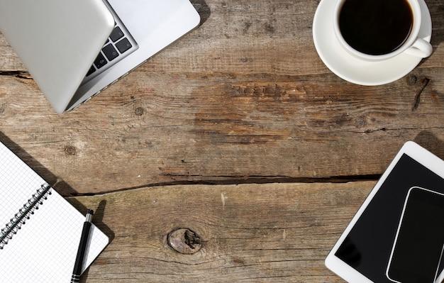 Computadora portátil, bloc de notas y bolígrafo sobre la mesa con una taza de café y con otros dispositivos