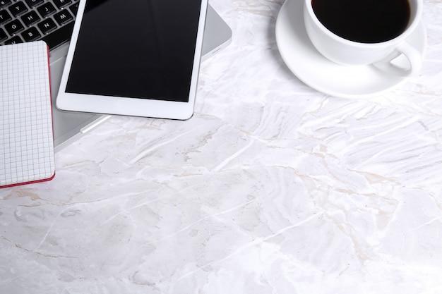 Computadora portátil, bloc de notas, tableta y una taza de café sobre la mesa
