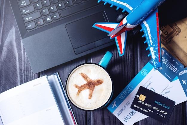 Computadora portátil, boletos de avión, café, tarjeta de crédito sobre la mesa