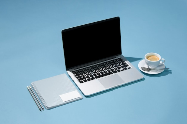 La computadora portátil, bolígrafos, teléfono, nota con pantalla en blanco en la mesa
