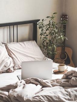 Computadora portátil y café en la cama y una guitarra al lado de la cama en el dormitorio