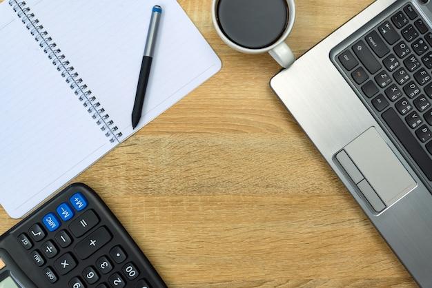 Computadora portátil, calculadora y taza de café en la mesa de trabajo