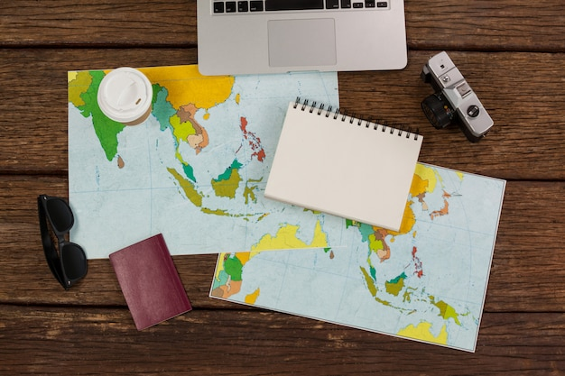 Computadora portátil, cámara, bloc de notas, mapas, pasaporte y viajero