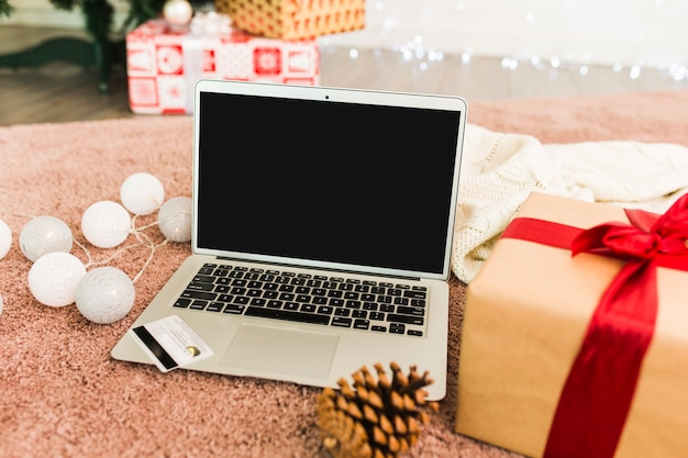 Computadora portátil cerca de la tarjeta de plástico, cajas actuales, gancho de abeto y luces de colores.