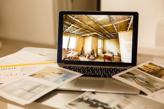 Computadora portátil en la construcción de papel de dibujo arquitectónico