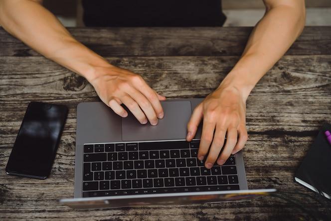 Computadora portátil en una mesa de madera, manos de un hombre que trabaja en una computadora