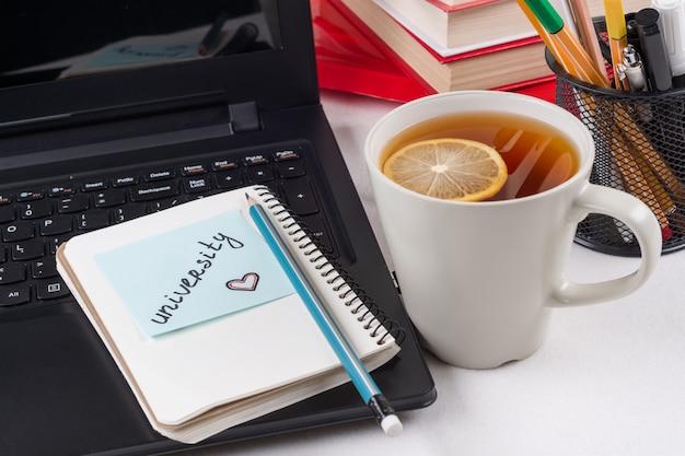 Computadora portátil en el escritorio del estudiante, en el monitor una pegatina con la palabra universidad.