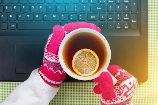 Computadora portátil, guantes, suéter, té caliente