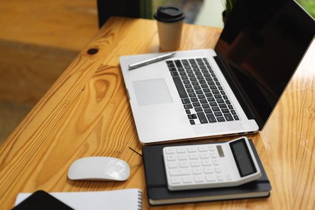 Computadora portátil con maqueta de pantalla vacía negra, calculadora y cosas en la mesa de madera
