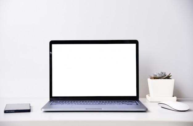 Computadora portátil moderna de pantalla en blanco con mouse y pequeña planta, escritorio de espacio de trabajo