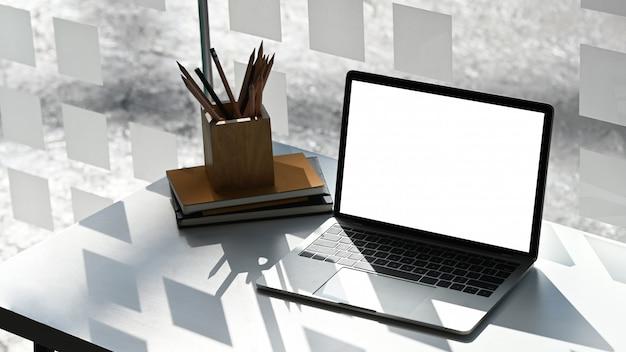 La computadora portátil de pantalla blanca está poniendo en el escritorio de trabajo blanco.