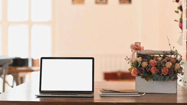 Computadora portátil con pantalla en blanco, cuaderno y ramo de rosas en una canasta de plástico blanco, todo esto sobre la mesa de madera con una moderna sala de estar