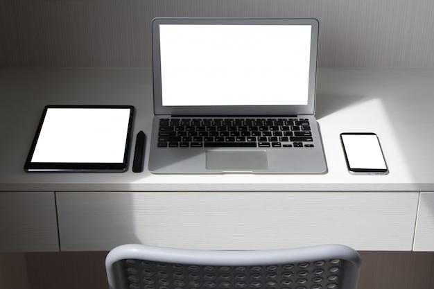 La computadora portátil con pantalla en blanco, el teléfono inteligente, la tableta digital y el lápiz óptico están en el escritorio de madera.