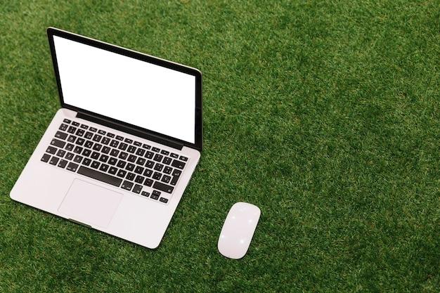 Una computadora portátil y un ratón abiertos en fondo de hierba artificial