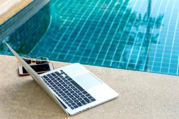 Computadora portátil y teléfono inteligente cerca de la piscina, el empresario moderno puede trabajar en cualquier lugar.