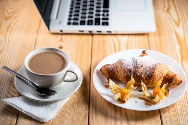 Computadora, taza de café y croissant en mesa de madera marrón