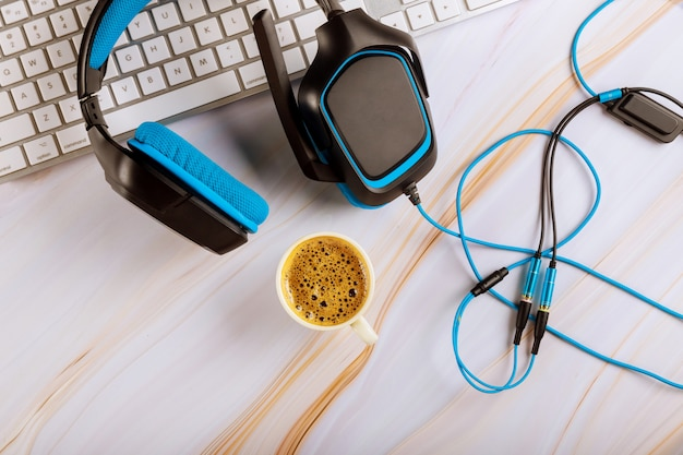 Computadora con teclado blanco con auriculares en un teléfono de atención al cliente trabajando en call center escritorio de oficina con taza de café
