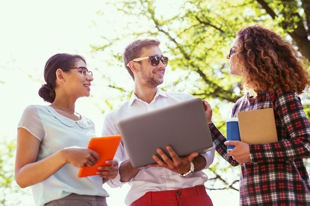 Comunicación agradable. exuberante joven sosteniendo su computadora portátil y discutiendo un nuevo proyecto con sus compañeros de grupo