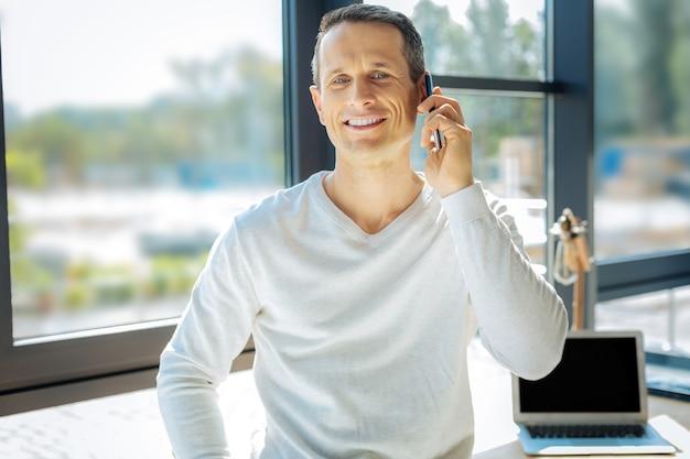 Comunicación agradable. feliz agradable hombre encantado sonriendo y hablando por teléfono mientras tiene una comunicación agradable