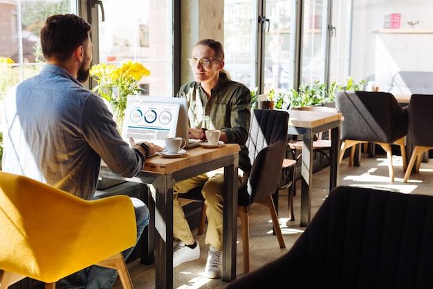 Comunicación agradable. hombres agradables agradables sentados uno frente al otro con sus computadoras portátiles mientras hablan