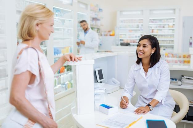 Comunicación agradable. persona de sexo femenino alegre manteniendo una sonrisa en su rostro mientras mira a su cliente
